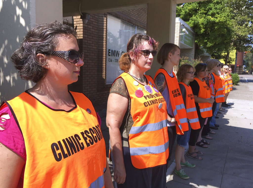 In this July 17, 2017 file photo, escort volunteers line up outside the EMW Women's Surgical Center in Louisville, Ky. Republican lawmakers outlined their next round of abortion legislation in Kentucky on Wednesday, Oct. 20, 20211 previewing efforts to strengthen parental consent standards for minors seeking the procedure and create greater oversight of medication-induced abortions.(AP Photo/Dylan Lovan, File)